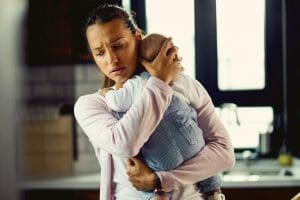 Young mother holding son thinking about child support
